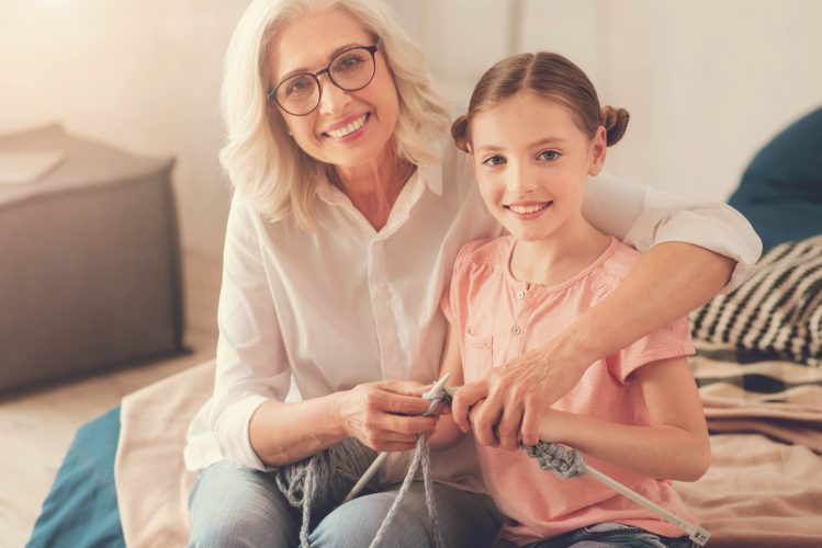 Useful skills. Cheerful positive cute girl holding knitting needles and learning to knit while being with her grandmother